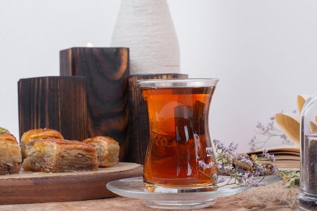 Copo de chá e várias baklavas tradicionais na mesa de mármore.