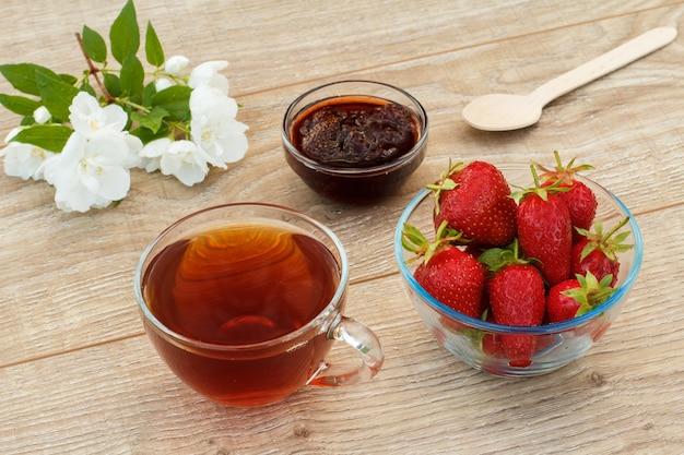 Copo de chá, geléia de morango caseira e morangos frescos em tigelas, colher e flores de jasmim brancas sobre fundo de madeira. vista do topo.