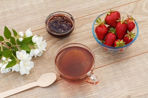 Copo de chá, geléia de morango caseira e morangos frescos em tigelas e flores de jasmim brancas em fundo de madeira. vista do topo.