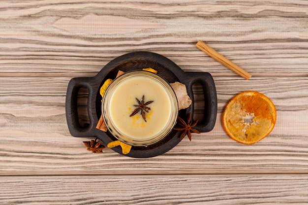 Copo de chá karak ou masala chai na vista de cima da mesa de madeira