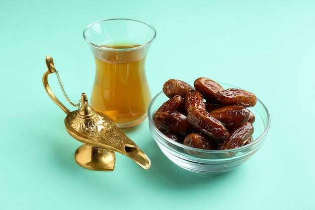 Copo de chá, lâmpada do ramadã e tâmaras na superfície da hortelã