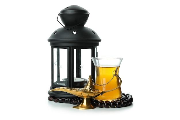 Copo de chá, lâmpada do ramadã, lanterna e rosário isolado na superfície branca