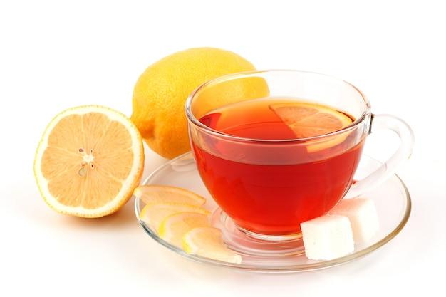 Copo de chá perto de dois limões amarelos.
