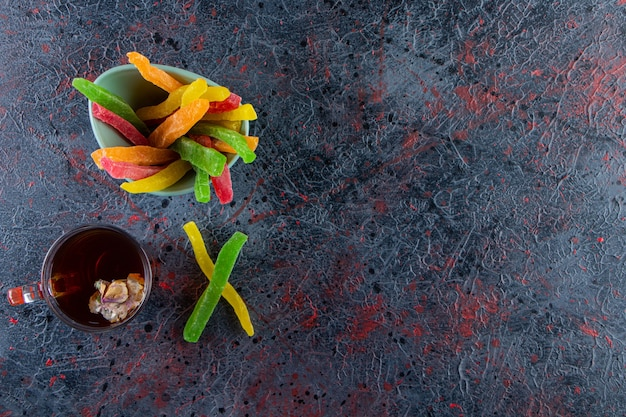 Copo de chá preto com tigela de doces coloridos em fundo escuro.