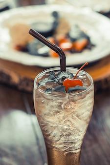 Copo de chá preto de gelo com cereja no topo da bebida para refresco fundo de sobremesa borrão na mesa