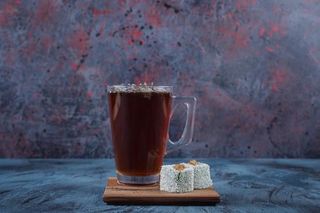 Copo de chá preto quente com delícias doces na superfície azul.