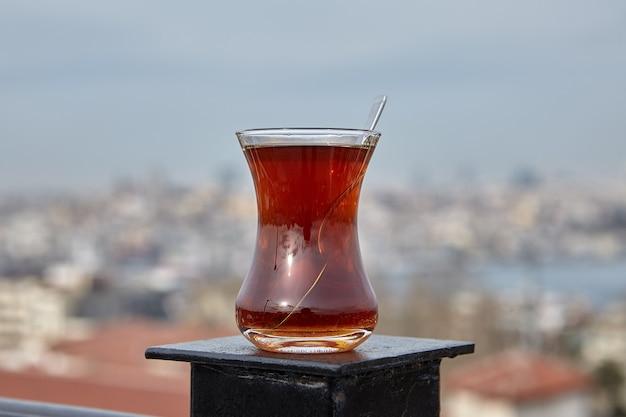 Copo de chá preto turco colocado na cerca do telhado, tendo como pano de fundo a paisagem urbana de istambul