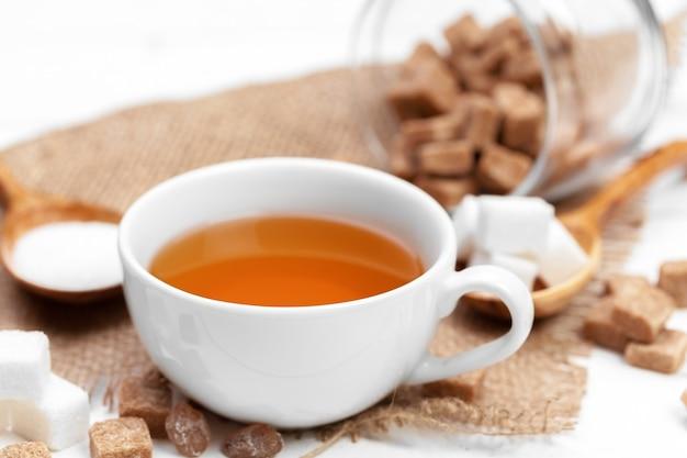 Copo de chá quente com açúcar em cima da mesa
