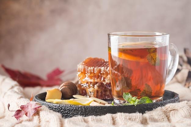 Copo de chá quente com mel de hortelã, gengibre e limão sobre fundo claro