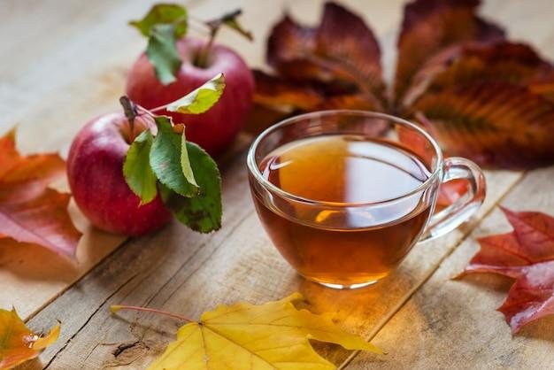 Copo de chá quente de vidro sobre uma mesa de madeira com folhas de outono e maçã