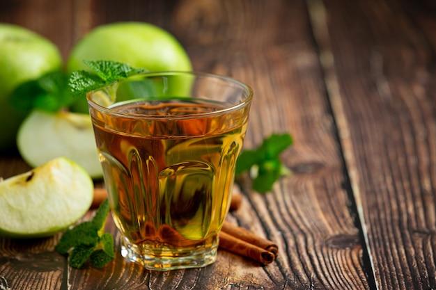 Copo de chá saudável de maçã verde colocado ao lado de maçãs verdes frescas