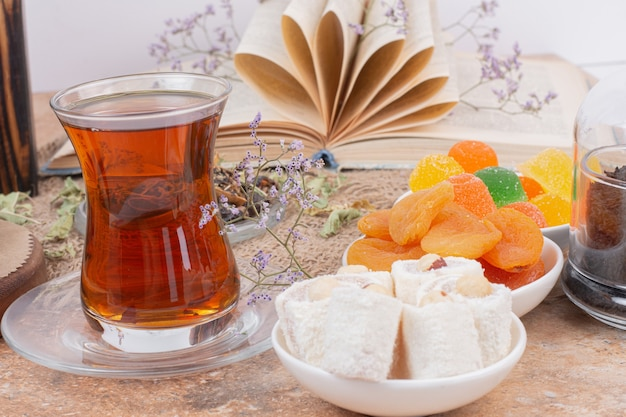 Copo de chá, vários doces e damascos secos na mesa de mármore.