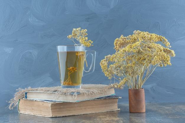 Copo de chá verde e flores em cima do livro.