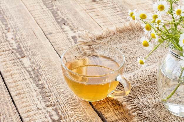Copo de chá verde e flores frescas de camomila branca em fundo de madeira.