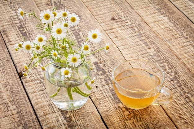Copo de chá verde e jarra com flores frescas de camomila branca no fundo