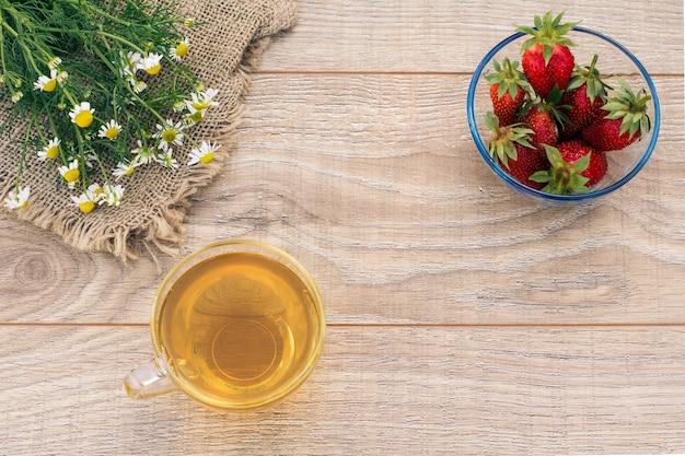 Copo de chá verde, flores de camomila e taças de vidro com morangos frescos no fundo de madeira.