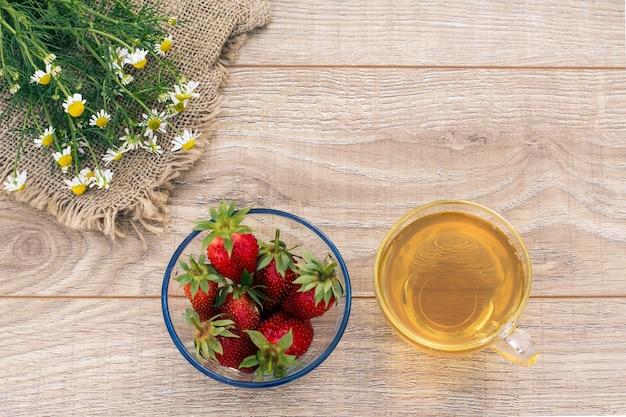 Copo de chá verde, flores de camomila, taças de vidro com flores secas de matricaria chamomilla e morangos frescos no fundo de madeira. vista superior com espaço de cópia.