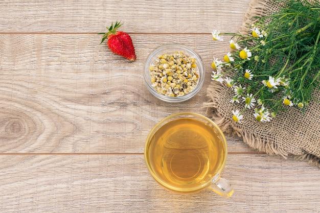Copo de chá verde, flores frescas de camomila, morango e uma pequena tigela de vidro com flores secas de matricaria chamomilla no fundo de madeira.