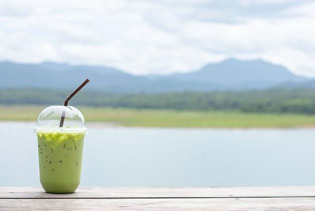 Copo de chá verde frio na mesa vistas embaçadas de fundo água e montanha.