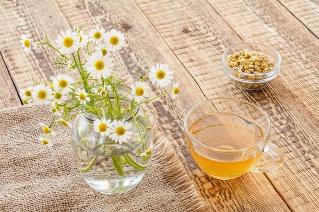 Copo de chá verde, jarra com flores de camomila branca em pano de saco e tigela de vidro com flores secas de matricaria chamomilla em fundo de madeira