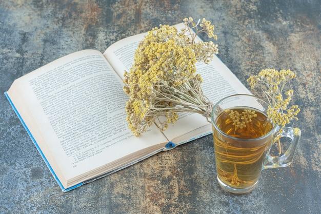 Copo de chá verde, livro e flores sobre fundo de mármore.