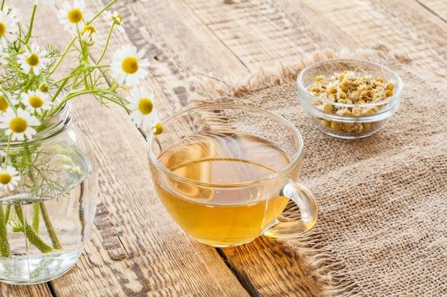 Copo de chá verde, pequena tigela de vidro com flores secas de matricaria chamomilla e flores frescas de camomila branca em fundo de madeira.