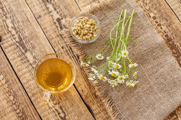 Copo de chá verde, tigela de vidro com flores secas de matricaria chamomilla e flores frescas de camomila branca em pano de saco e fundo de madeira velho. vista do topo.