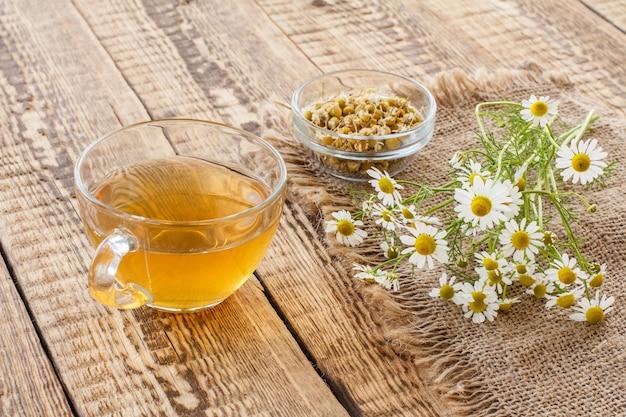Copo de chá verde, tigela de vidro com flores secas de matricaria chamomilla e flores frescas de camomila branca em pano de saco e fundo de madeira velho.