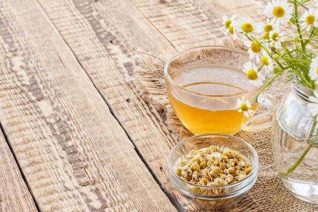 Copo de chá verde, tigela de vidro com flores secas de matricaria chamomilla e flores frescas de camomila branca em saco e fundo de madeira.
