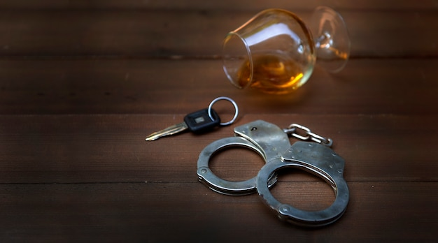 Copo de chaves do carro de conhaque e algemas. conceito para beber dirigindo