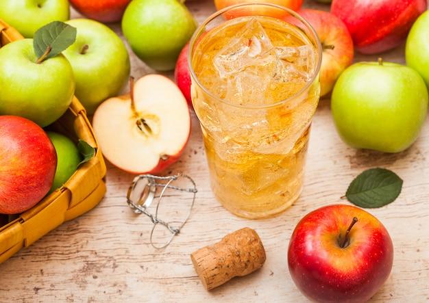 Copo de cidra de maçã orgânica caseira com maçãs frescas na cesta de bambu na mesa de madeira, copo com cubos de gelo