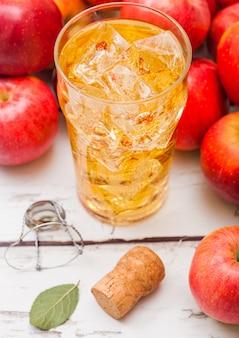 Copo de cidra de maçã orgânica caseira com maçãs frescas na mesa de madeira, copo com cubos de gelo