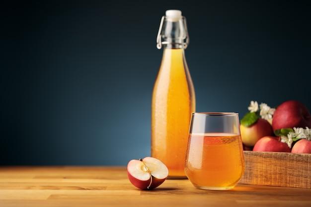 Copo de cidra ou suco de maçã caseiro, maçãs vermelhas frescas do jardim e uma garrafa no fundo
