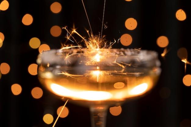 Copo de close-up com champanhe e luzes douradas