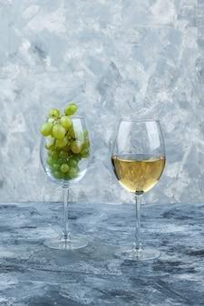 Copo de close-up de uvas brancas com copo de uísque em fundo de mármore azul claro e escuro. vertical