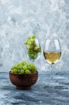 Copo de close-up de uvas brancas com copo de uísque, tigela de uvas, toalha de cozinha em fundo de mármore azul claro e escuro. vertical