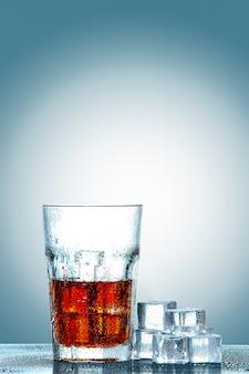 Copo de coca-cola com cubos de gelo
