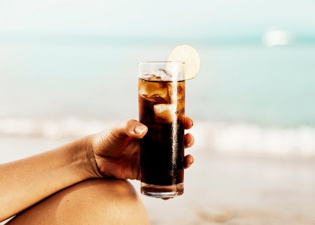 Copo de coca-cola com gelo na mão na praia