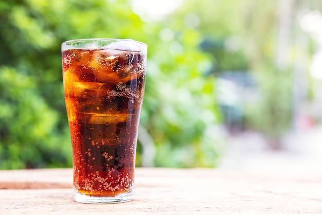 Copo de coca-cola com gelo na mesa de madeira, refrigerante. copie o espaço.