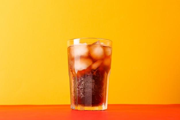 Copo de coca-cola fria contra a cor de fundo, espaço para texto