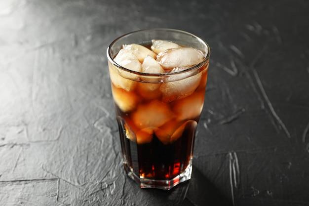 Copo de coca-cola fria em fundo preto de cimento