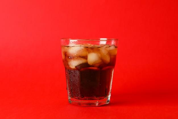 Copo de coca-cola fria sobre fundo vermelho, espaço para texto