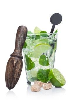 Copo de cocktail alcoólico de verão mojito com cubos de gelo de hortelã e limão em fundo branco. com lima crua e espremedor de madeira com cana-de-açúcar