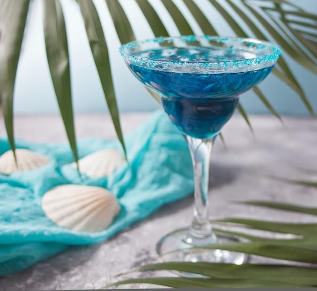Copo de cocktail azul sob uma folha de palmeira