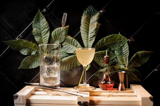 Copo de cocktail com cocktail de verão amarelo, garrafa com licor vermelho e utensílios de bar no fundo das folhas verdes