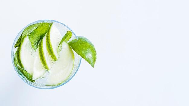 Copo de cocktail com fatias de limão e hortelã