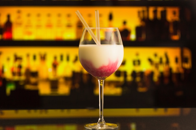 Copo de cocktail com garrafas no fundo