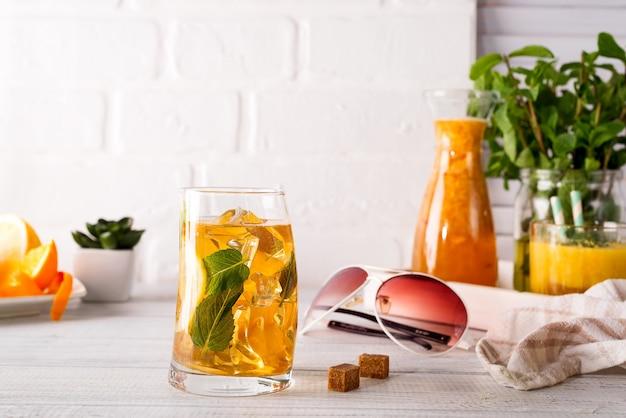 Copo de cocktail com gelo, hortelã e gengibre em um backgorund de madeira branco