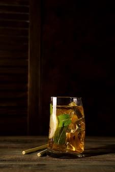 Copo de cocktail com gelo, hortelã e gengibre em um backgorund de madeira escura