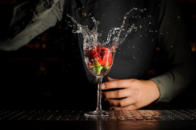 Copo de cocktail com salpicos de bebida alcoólica e botão de rosa